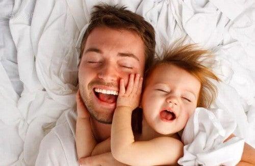 Ojciec bawiący się z córką w łóżku