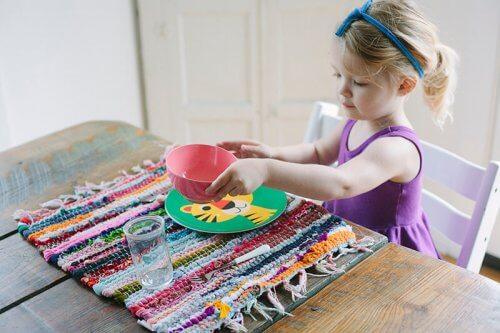 Przydzielenie dzieciom obowiązków domowych - dziewczynka nakrywa stół
