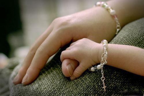 Ręce dziecka trzymają mamę za palec