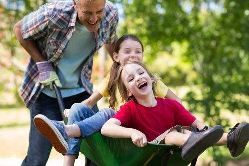 Roześmiany tata wiozący na taczce dwie śmiejące się córki