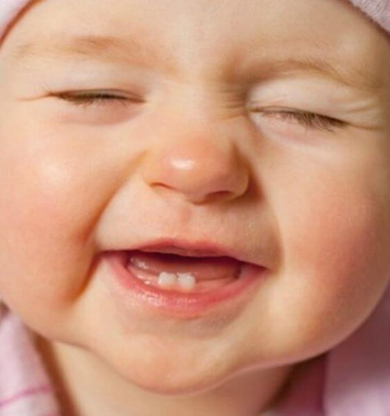 Śmiejące się niemowlę z dwoma ząbkami
