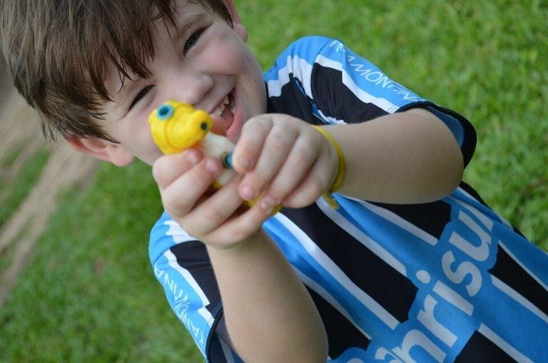Śmiejący się chłopiec celujący wodnym pistoletem w obiektyw - jak pracuje mózg dziecka podczas zabawy
