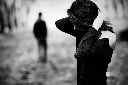 Smutna kobieta z twarzą zakrytą włosami, w tle sylwetka odchodzącego mężczyzny - cierpienie emocjonalne po odejściu rodzica