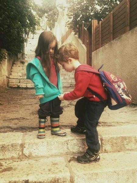 Starszy brat zapina kurtkę siostrze