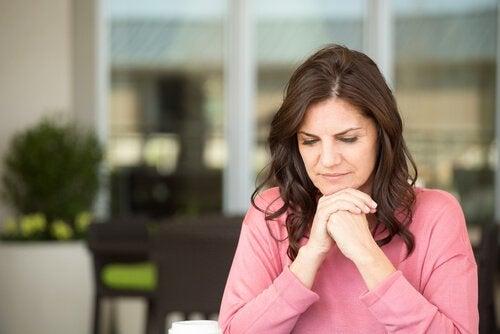 Szatynka w różowym swetrze opierająca brodę na złączonych dłoniach