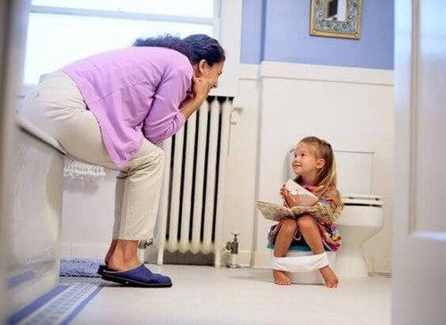 Mama rozmawiająca do córki siedzącej na nocniku