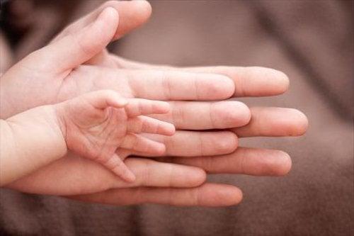 Trzy dłonie nałożone na siebie: mamy, taty i dziecka - rodzenie chłopca boli bardziej niż rodzenie dziewczynki