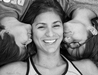 Uśmiechnięta mama leżąca między dwoma synami - małe rzeczy, które można zrobić dla dziecka