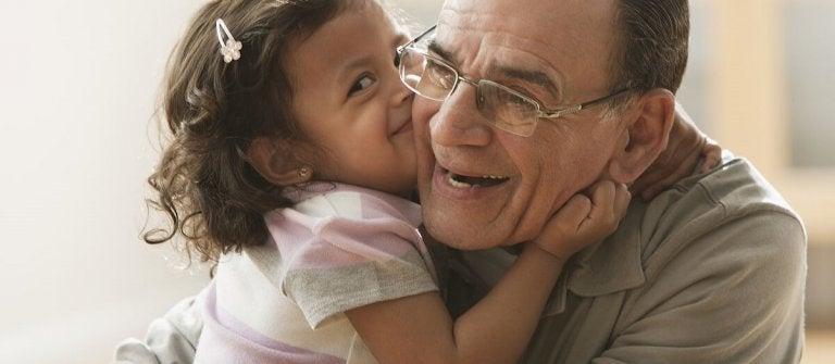 Uśmiechnięta dziewczynka przytulająca się do dziadka i całująca go w policzek - dawanie całusów przez dziecko