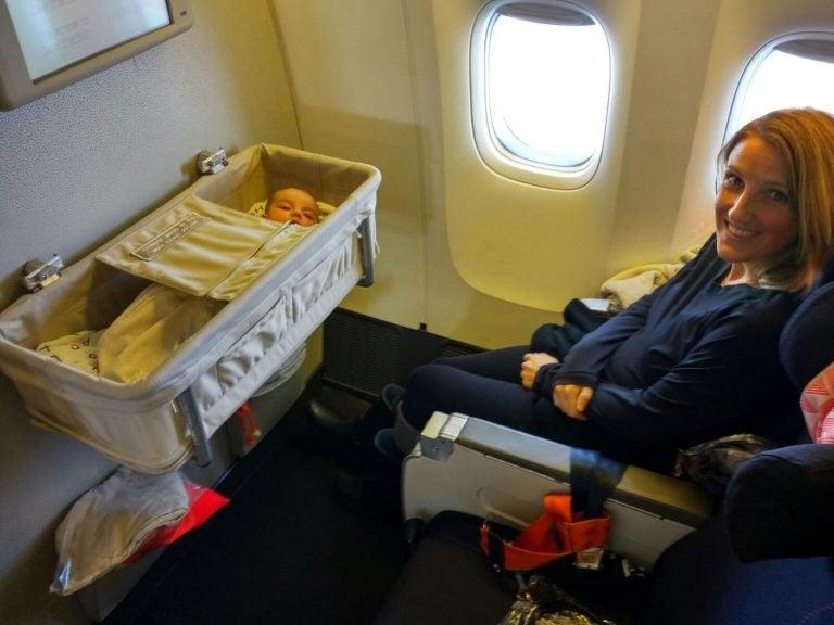 Uśmiechnięta mama w samolocie z dzieckiem śpiącym w kołysce - podróżowanie z niemowlęciem