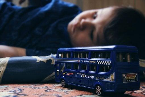 Zabawka autobus w tle chłopiec leżący na podłodze