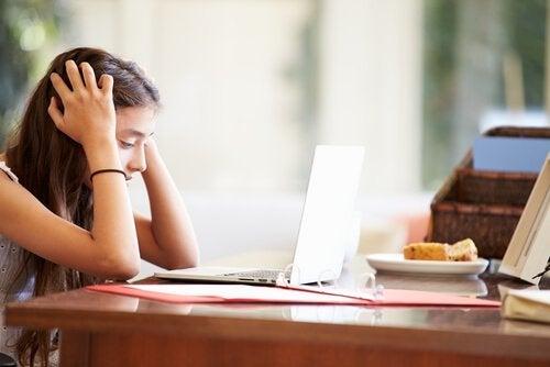 Zmartwiona dziewczynka z głową trzymaną w rękach siedząca przy stole przed laptopem
