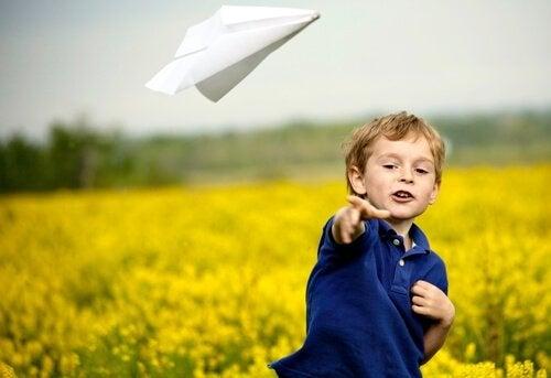 Chłopiec puszcza papierowy samolocik