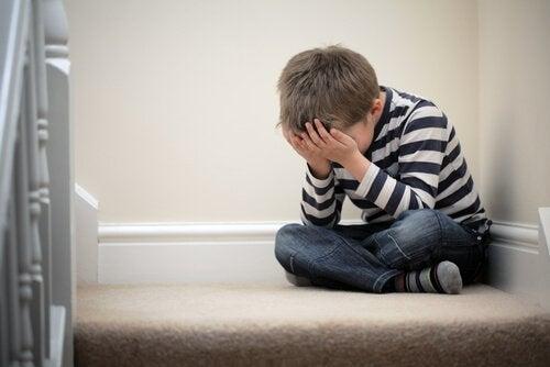 Chłopiec siedzący w kącie z twarzą schowaną w dłoniach - brak zabawy źle działa na dzieci