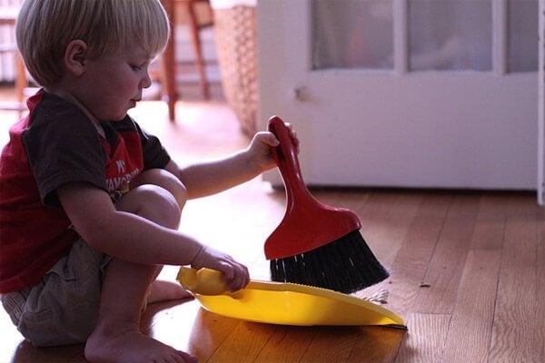 Chłopiec z szufelką i zmiotką zamiatający podłogę