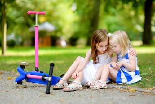 Dwie przytulające się dziewczynki siedzące na ziemi obok porzuconych hulajnóg