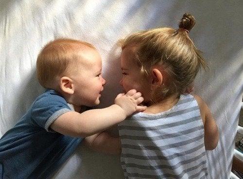 Dziewczynka i chłopiec przytulający się leżąc na łóżku - rozwijanie inteligencji emocjonalnej