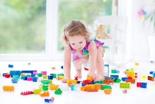 Dziewczynka w kolorowej sukience bawiąca się klockami na podłodze - rozwój motoryczny dziecka