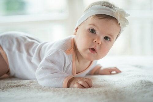 Dziewczynka z opaską na głowie raczkująca po dywanie - szósty miesiąc życia dziecka to początek raczkowania