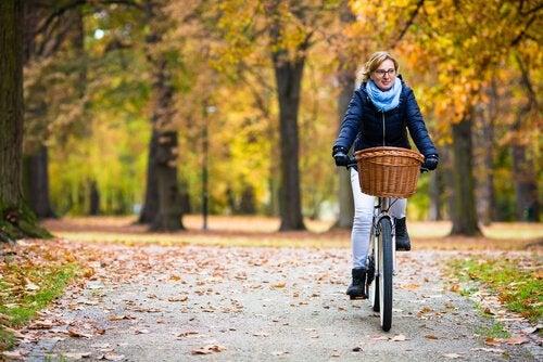 Kobieta jadąca na rowerze po jesiennym parku