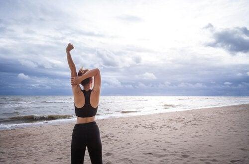 Kobieta w sportowym stroju stojąca tyłem i rozciągająca się na plaży