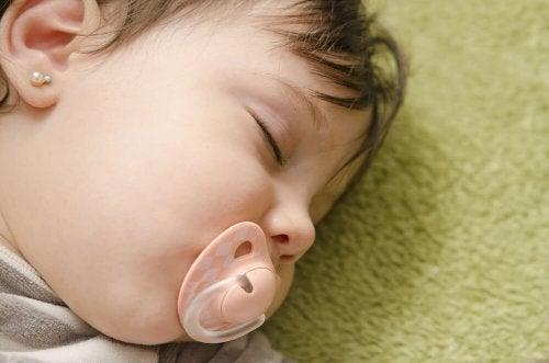 Kolczyki dla niemowląt - dziewczynka śpi ze smoczkiem