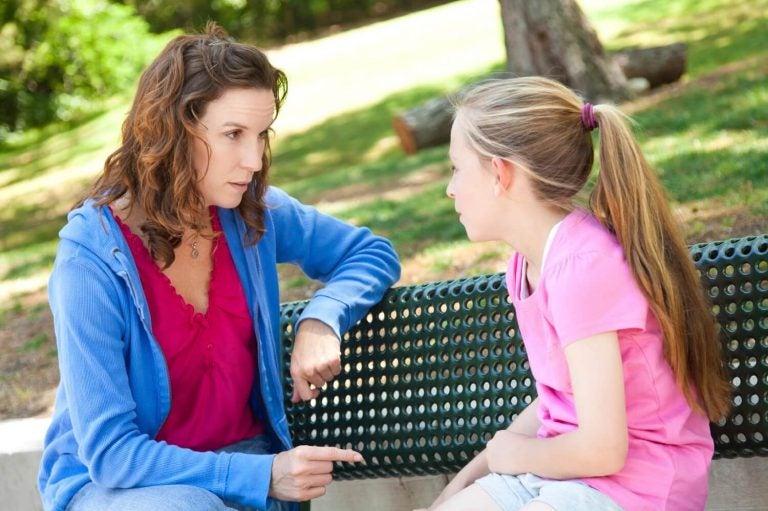 Mama i córka siedzące na ławce w parku i rozmawiające ze sobą