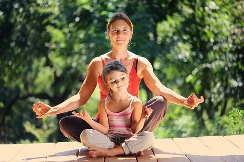 Mama i córka siedzące w pozycji lotosu na tarasie