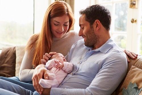 Mama i tata siedzący na kanapie, uśmiechający się do przytulanego noworodka