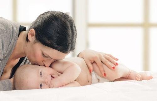 Rodzicielstwo bliskości-mama całuje dziecko