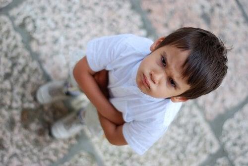 Naburmuszony chłopiec z rękoma założonymi na klatce piersiowej