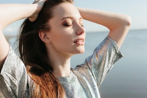 Relaksująca się kobieta z zamkniętymi oczami i dłońmi we włosach