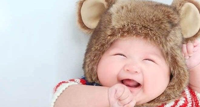 Roześmiane niemowlę w czapce z uszami misia - piąty miesiąc życia dziecka to zwiększone interakcje z otoczeniem