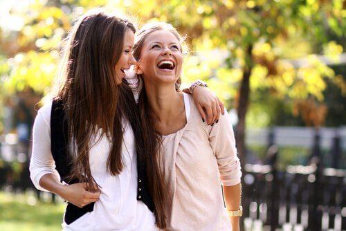 Roześmiane szatynka i blondynka idące razem przez park - by być lepszą mamą spędzaj czas z przyjaciółmi