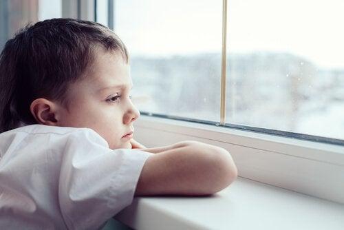 Smutny chłopiec wyglądający przez okno z rękoma opartymi na parapecie