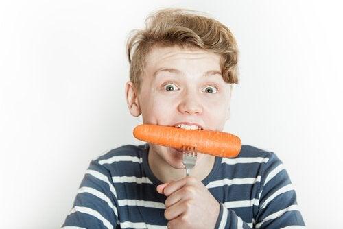 Chłopak je marchewkę