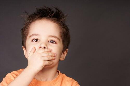 Chłopiec zakrywa usta