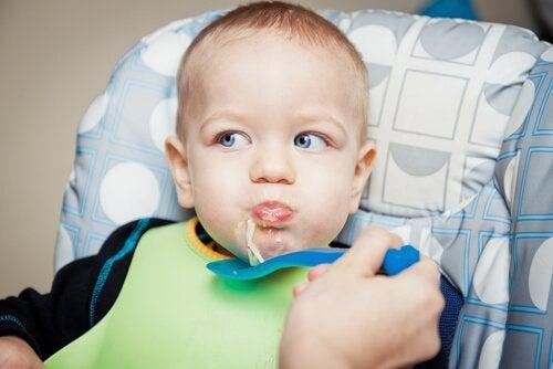 Dziecko karmione łyżką zupą z makaronem