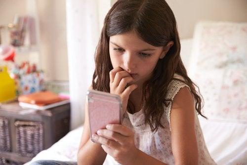 Dziewczynka siedząca na łóżku, wpatrzona w telefon i gryząca paznokcie