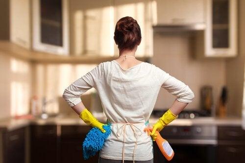 Kobieta w rękawicach do sprzątania podpierająca się pod bokami