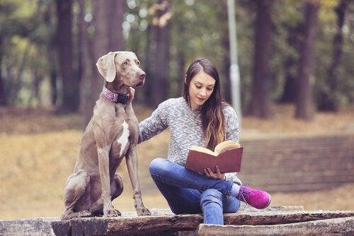 Książki dla młodzieży - dziewczyna czyta z psem w parku