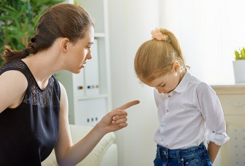 Mama grożąca palcem dziewczynce stojącej ze spuszczoną głową