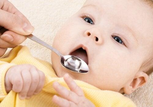 Mama ppodająca dziecku lekarstwo na łyżeczce - zapobieganie grypie