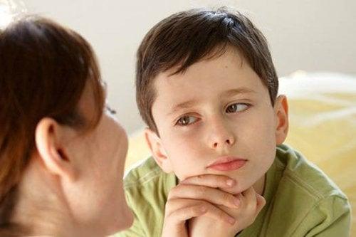 Mama rozmawiająca z chłopcem podpierającym głowę na rękach - jak powinno wyglądać odmawianie dziecku