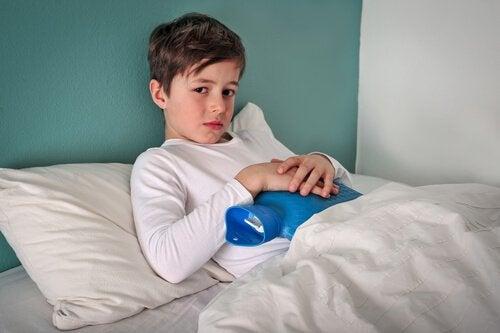 Smutny chłopiec leżący w łóżku z termoforem na brzuchu