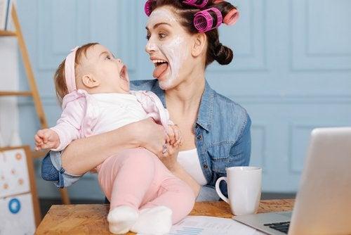Zapewnić rozrywkę dziecku - mama w maseczce na twarzy rozśmiesza niemowlę