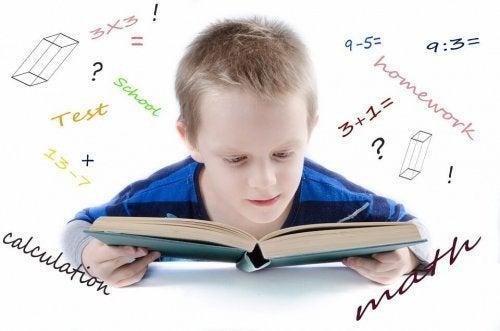 Chłopiec siedzący nad książką, otoczony równianiami - jak nauczyć dziecko mnożenia