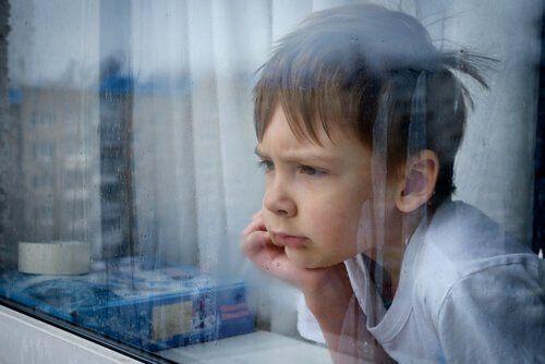 Chłopiec zamyślony patrzy przez okno