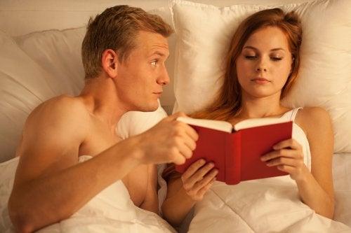 Kobieta czyta książkę, a mężczyzna chce się kochać