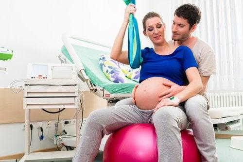 Kobieta w ciąży siedząca razem z partnerem na dmuchanej piłce - pozycje do porodu